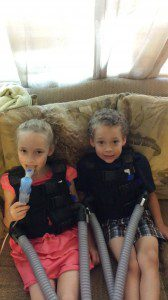 """London and Nathaniel """"doing their vest."""" Each of them wears an inCourage vest for about 30 minutes each day to keep their lungs free of mucous. London also takes medication through a nebulizer."""