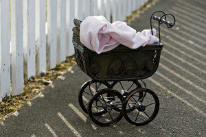 vintage stroller with blanket in front of white fence