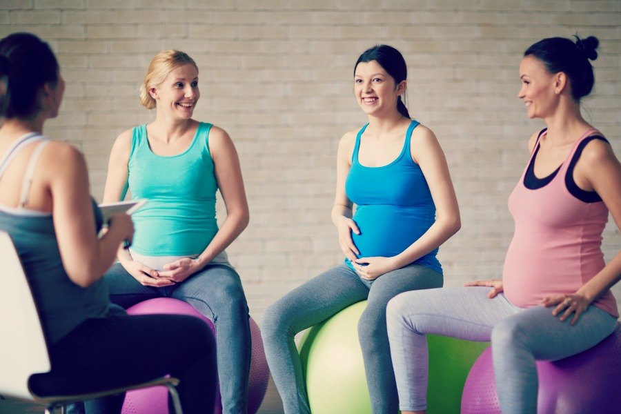 Group of pregnant women interacting in gym